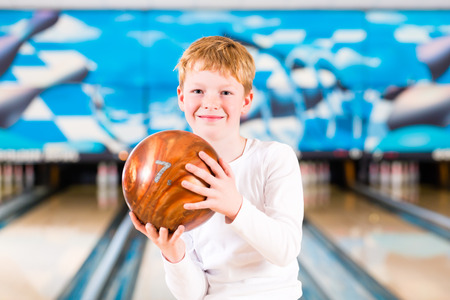Child bowling with ball in alley photo