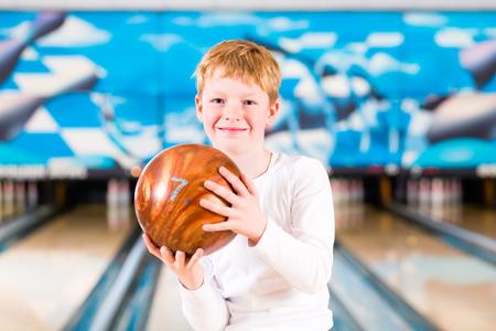 bolos: Niño con la bola de bowling en el callejón