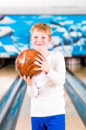 bolos: Ni�o con la bola de bowling en el callej�n