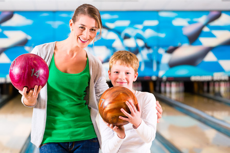 bowling alley: Mother and son playing together at bowling center