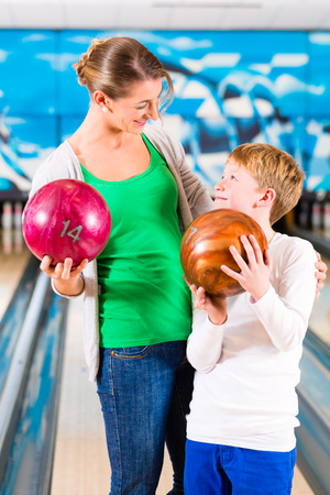 child ball: Mother and son playing together at bowling center