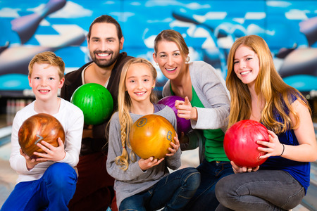 Parents playing with children together at bowling center Banque d'images