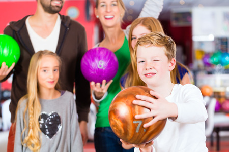 bowling: Parents playing with children together at bowling center Stock Photo