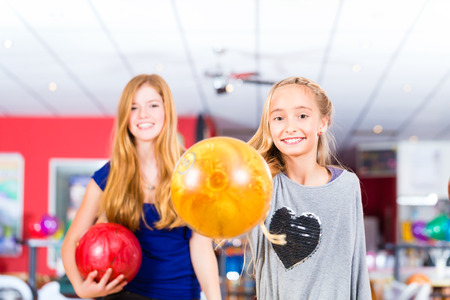 Children Friends playing together at bowling center photo