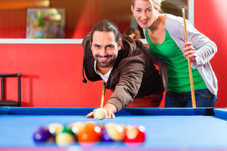 pool table: Couple or friends playing billiard with queue and balls on pool table