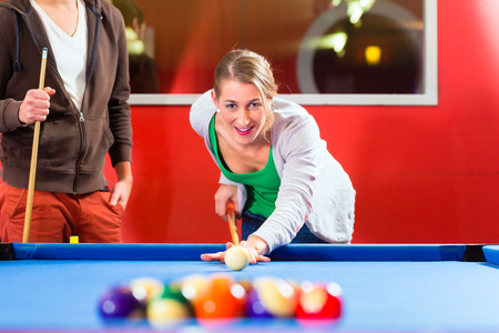 pool halls: Couple or friends playing billiard with queue and balls on pool table