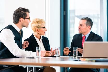 negociacion: Asunto - reuni�n en la oficina, los empresarios est�n discutiendo un documento en el ordenador port�til y trabajar como equipo Foto de archivo