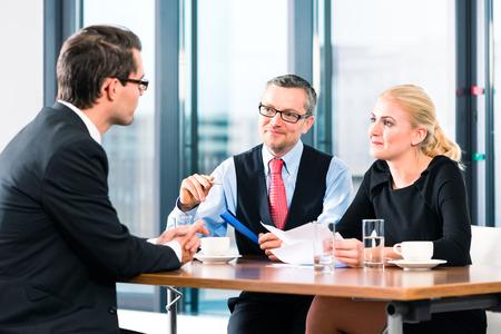 entrevista de trabajo: Negocios - hombre joven en una entrevista de trabajo, firma su contrato de trabajo con el jefe y su asistente femenina en su oficina Foto de archivo