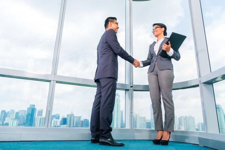 indonesia people: Low angle view of Asian business partners shaking hands Stock Photo