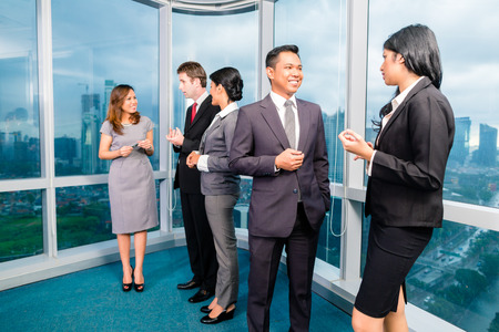 indonesia people: Asian Businesspeople standing and talking in front of office window Stock Photo