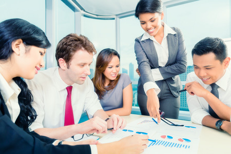 Asian Businesspeople anaylzing graph in office Stock Photo