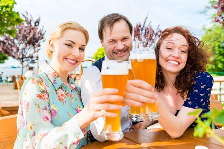 Freunde Toasten mit Bier im Biergarten