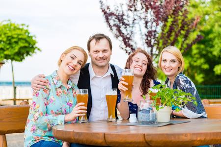 friends drinking: Friends toasting with beer in garden restaurant