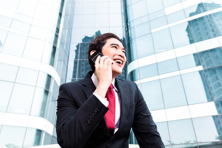 telephoning: Asian businessman telephoning with smartphone in front of tower building
