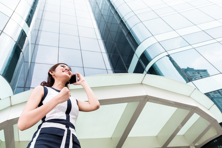 telephoning: Asian businesswoman telephoning wit smartphone in front of tower building