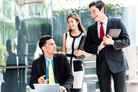 hombres trabajando: Mujer de negocios asiática y hombres que trabajan fuera en el ordenador