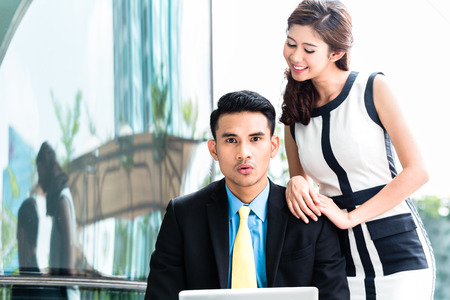 indonesian people: Asian business woman sexually harassing man in public