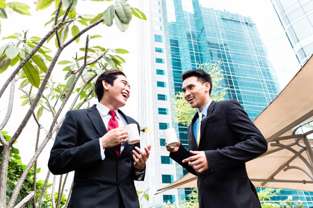 chitchat: Asian business men having coffee break in front of tower building