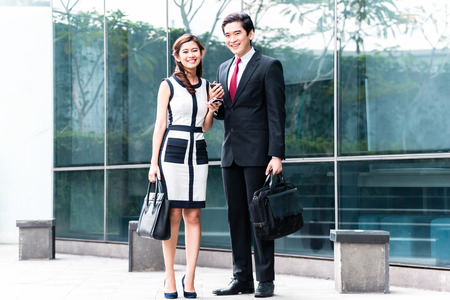 Asian business woman and man going arm in arm to work in front of building