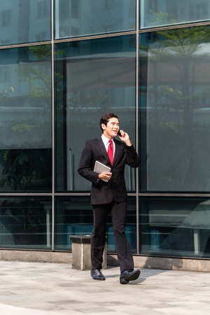 telephoning: Asian businessman telephoning with mobile phone in front of building Stock Photo