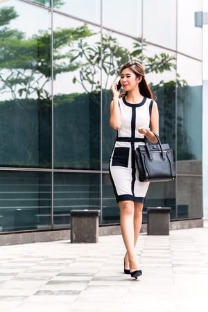 telephoning: Asian businesswoman telephoning with mobile phone in front of building Stock Photo