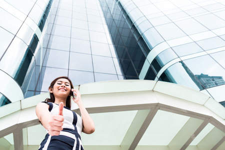 wit: Asian businesswoman telephoning wit smartphone in front of tower building