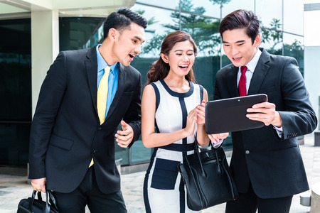 Asian business woman and men working outside on tablet computer in front of tower building