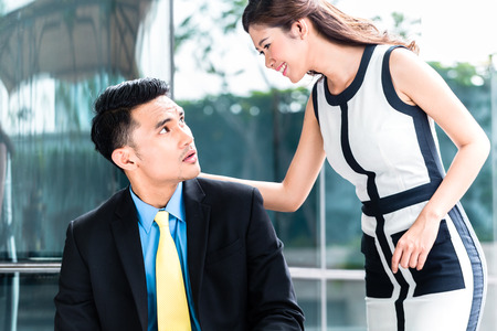 harassing: Asian business woman sexually harassing man in public
