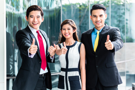 Asian business woman and men outside in front of building photo