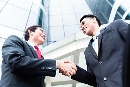 Asian business men outside in front of tower building shaking hands