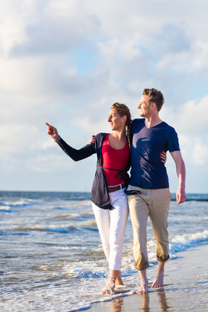 baltic sea: Couple take a romantic walk through sand and waves at German north sea beach Stock Photo