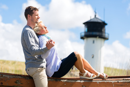 Couple having romantic vacation in German north sea beach dune in front of lighthouse photo