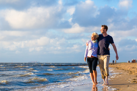 Couple take a romantic walk through sand and waves at German north sea beach Stockfoto