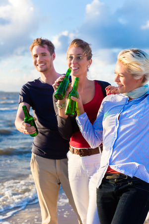 friends drinking: Friends enjoying bottled beer at sunset on German north sea beach