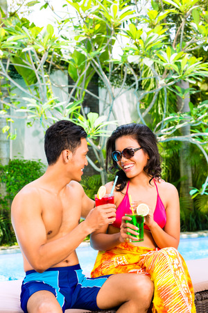 all smiles: Asian couple drinking fancy cocktails at hotel or club pool