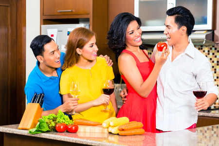 Asian friends cutting vegetables cooking together in domestic kitchen for dinner party, drinking wine photo
