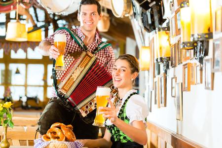 Bayerisches Restaurant mit Musik, Gäste, Weißbier und Brezel