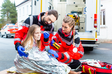 Emergency doctor and paramedic or ambulance team helping accident victim photo