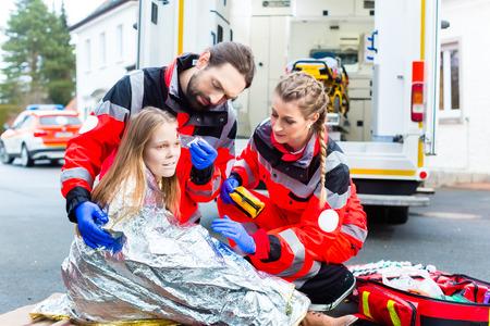 emergencia: M�dico de emergencia y equipo de param�dicos o una ambulancia ayudar v�ctima de accidente Foto de archivo