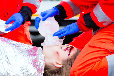 working accident: Emergency doctor and nurse or ambulance team giving oxygen to accident victim