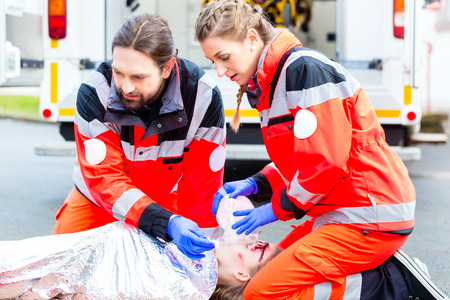 Emergency doctor and nurse or ambulance team giving oxygen to accident victim photo