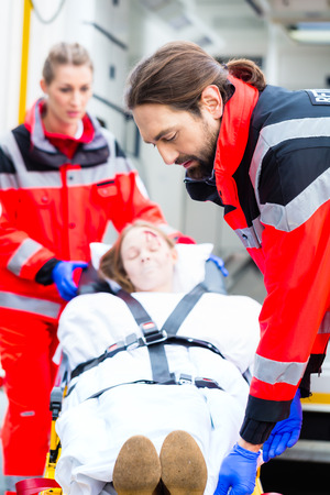 emergency stretcher: Emergency doctor and nurse or ambulance team transporting accident victim on stretcher