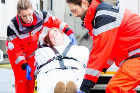 personas ayudando: M�dico de emergencia y la enfermera o ambulancia equipo de transporte de v�ctima de accidente en camilla Foto de archivo