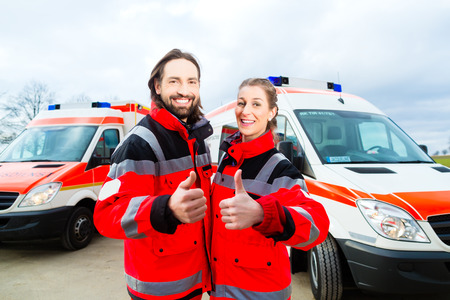 rescuing: Emergency doctor and nurse standing in front of ambulance Editorial
