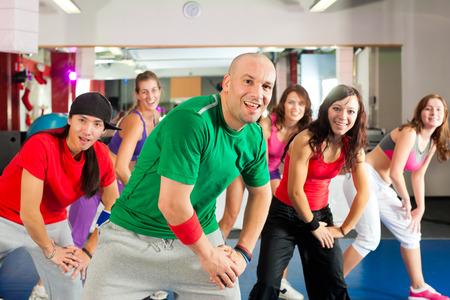 Fitness - Los jóvenes haciendo el entrenamiento de la danza o el entrenamiento de la danza en un gimnasio