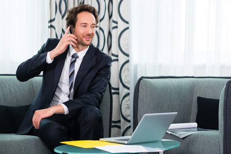 dossier: Businessman working in business hotel, he discusses some documents with a customer on the phone Stock Photo