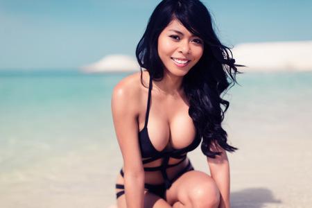 Girl kneeling on beach in water photo