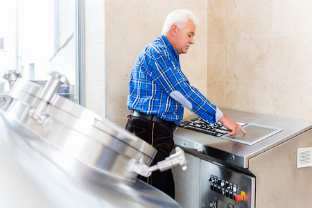 beer production: Brewer in brewhouse of beer brewery