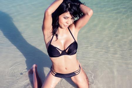 kneeling woman: Sexy Asian woman on beach vacation kneeling in water wearing swimwear