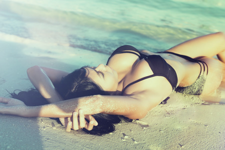 Sexy woman in beach vacation lying in sand in the waves, filtered pic photo